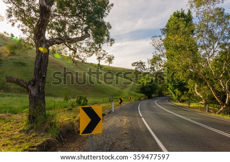 Rural Australian curvy road in the hills along countryside - stock photo