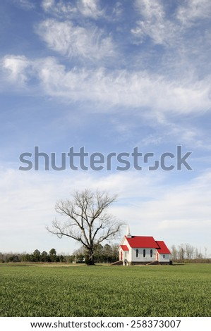 Rural Church with Bright Red Roof on Sunny Day - stock photo
