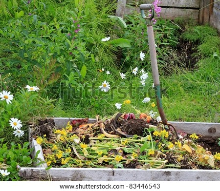 Rural compost pile with a rustic pitch fork and flowers in the background - stock photo
