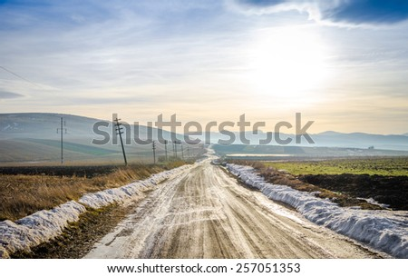 Rural countryside unpaved gravel road on a cold spring winter day with fields and snow and a contrasty filtered look - stock photo