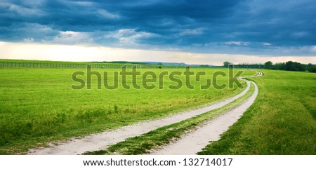 Rural dirt road in the filed landscape - stock photo
