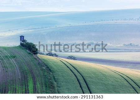 Rural Europe background - Moravian rolling landscape with hunting tower shack in early morning on sunrise. Moravia, Czech Republic - stock photo