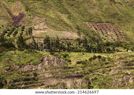 Rural hillside landscape with buildings, scrubs and trees along the road between Ambato and Banos in Tungurahua Province in Central Ecuador - stock photo