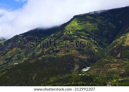 Rural hillside landscape with forests, small farms and orchards along the road between Ambato and Banos in Tungurahua Province in Central Ecuador - stock photo