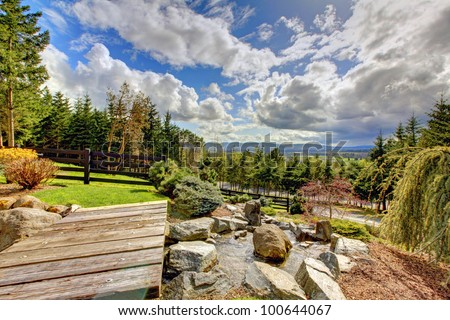 Rural home estate landscape with waterfall and dramatic sky. - stock photo