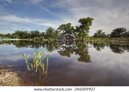Rural house with river reflection during daytime. - stock photo