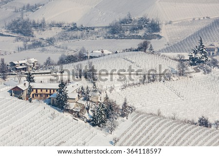 Rural houses on snowy hills in Piedmont, Northern Italy. - stock photo