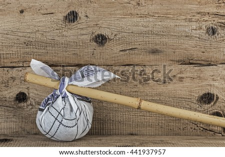 Rural knapsack on a bamboo pole on a old wooden background - stock photo