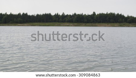 rural lake with forest line in summer day, sunny  - stock photo