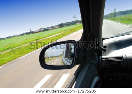 Rural landscape in the side-view mirror of a speeding car - stock photo