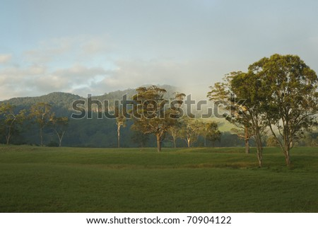 Rural landscape, sun rises with morning mist crossing in distance, Kangaroo Valley, Australia. - stock photo
