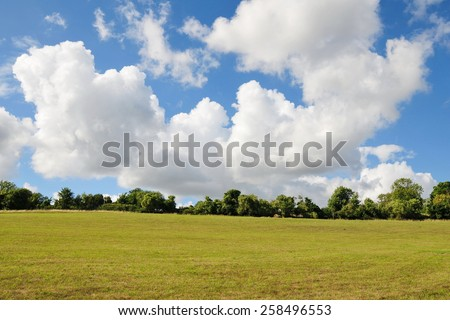 Rural Landscape View of an Open Green Field and Dramatic Cloudy Sky in the Avon Valley near Bath in Somerset England - stock photo