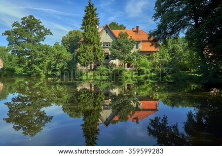 Rural landscape with a pond and the palace in Poland