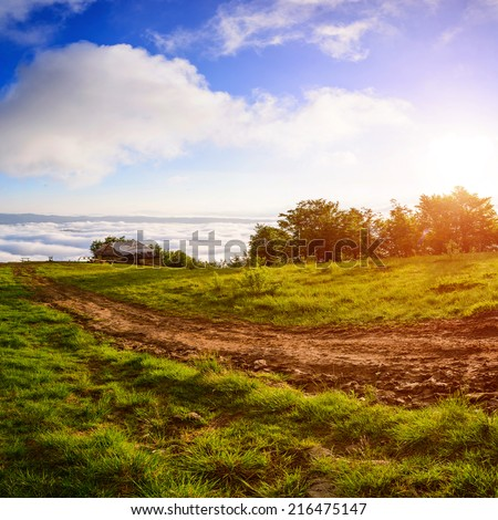 rural landscape with old house on the field over mountains  - stock photo