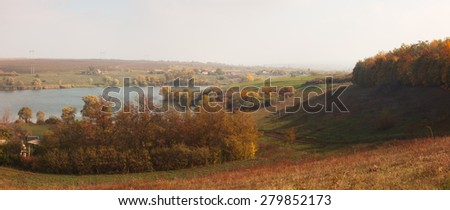 Rural landscape with river. View of village from hill. Shadow of trees. Sunny autumn morning - stock photo