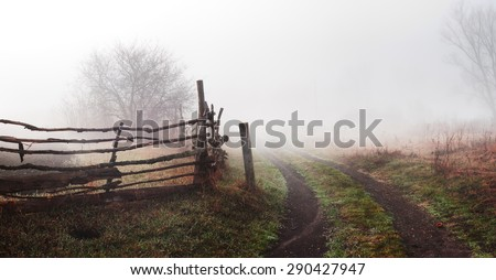 Rural landscape with road and fence. Wooden fence and tree in  fog. Spring morning. Loneliness, sad mood - stock photo