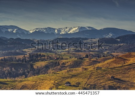 Rural landscape with traditional Romanian neighborhoods in the valleys of Bucegi mountains uphill in Sirnea village, Brasov county, Romania. - stock photo
