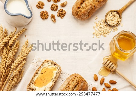 Rural or country breakfast - bread rolls, honey jar, milk, nuts, wheat on white wood from above. Background layout with free text space. - stock photo
