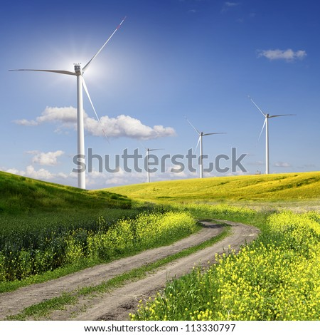 Rural road across the field to wind power - stock photo