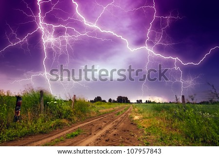 Rural road and lighting storm - stock photo