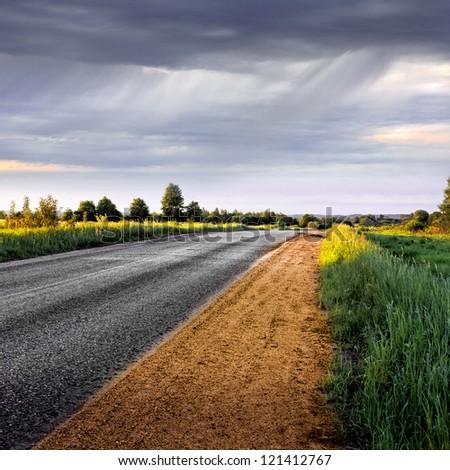 Rural road  before the rain. Panorama. Rural landscape. - stock photo