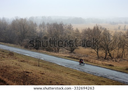Rural road in fog. Motorcyclist rides on wet road after rain. Landscape with fields and meadows. Rainy weather, sad mood - stock photo