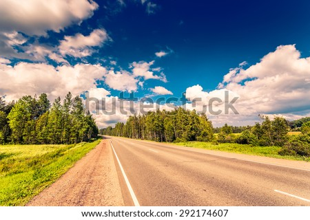 Rural road in the woods cloudy day. Image in the orange-blue toning - stock photo