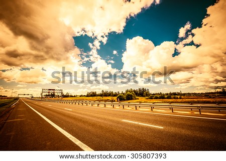 Rural road passing by a gas station. View from the road, image vignetting and the yellow-orange toning - stock photo