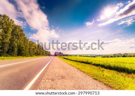 Rural road passing through fields and woods illuminated by the sun. View from the road, image in the orange-purple toning - stock photo