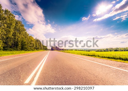 Rural road passing through fields and woods illuminated by the sun. View from the road, image in the soft orange-purple toning - stock photo