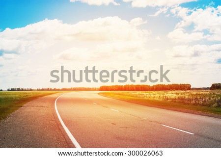 Rural Road with Turn and Clouds on Blue Sky. Nearby Wood. Sunny effect - stock photo