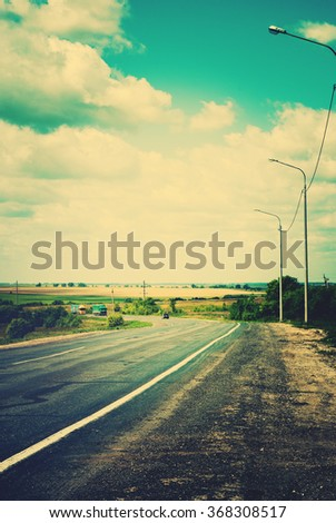 Rural Russian Landscape Road. Clouds on Horizon Sky. Toned - stock photo