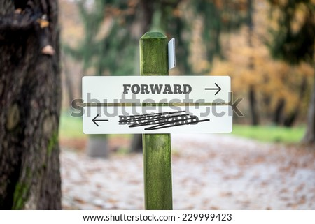 Rural signboard with two signs saying - Forward - Backward - pointing in opposite directions with the sign saying Backward scribbled through and an arrow pointing to the route forwards to success. - stock photo