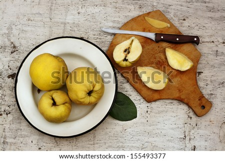 Rural still life ripe yellow quince fruits on the plate and cut fruit on plate with knife - stock photo