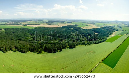Rural summer landscape with green grass field and rainy clouds - stock photo