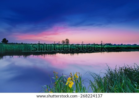Rural summer sunrise landscape with river and dramatic colorful sky - stock photo