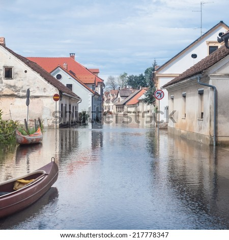 Rural village houses in floodwater. Road with the river overflown with the residents in their homes. River Krka floods and flooding the streets. Natural disaster in Kostanjevica, Slovenia.   - stock photo