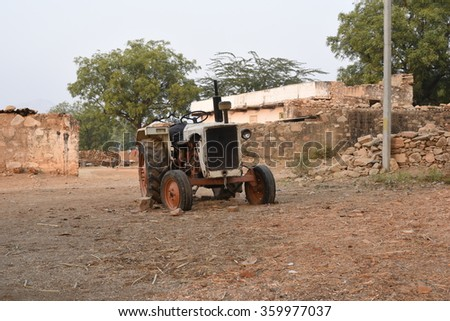 Rural village setting with an abandoned tractor, rural homes in backdrop - stock photo