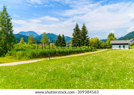 Rural walking path along green meadow in summer landscape of Alps Mountains, Weissensee lake, Austria - stock photo