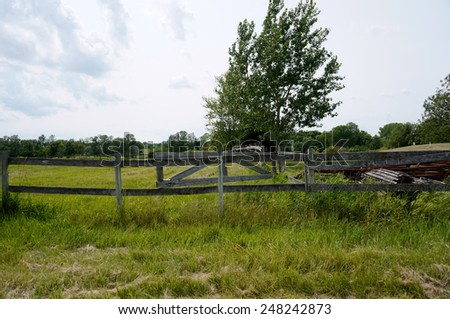 Rural yard and fence a couple homes slightly visible in distance - stock photo