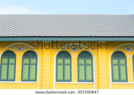 Rural yellow wooden house with blue sky - stock photo