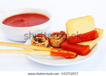 Rusks with sesame seeds, bread sticks and red sauce isolated on gray  background. - stock photo