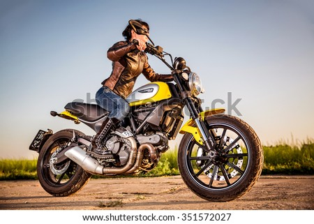 RUSSIA-AUGUST 11, 2015:Biker girl on a Scrambler Icon Ducati. A new Scrambler was introduced at the 2014 Intermot motorcycle show.Ducati is an Italian company that designs and manufactures motorcycles - stock photo
