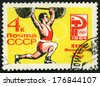 RUSSIA - CIRCA 1964: post stamp printed in USSR (soviet union) shows man weight lifter, 18th Olympic games Tokyo, Russian Olympic emblem, Scott 2922 A1465 4k red yellow, circa 1964 - stock photo