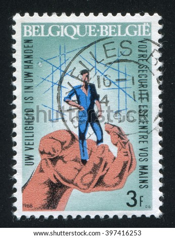 RUSSIA KALININGRAD, 20 OCTOBER 2015: stamp printed by Belgium, shows Hand Guarding Worker, circa 1968 - stock photo