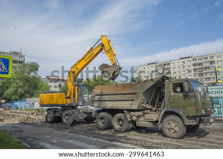 Russia Krasnoyarsk on July 21, 2015: preparatory work on replacement of a heating main, preparation for a heating season, loading of soil in the dump truck - stock photo
