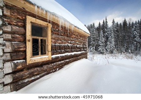 Russia log house in winter, with fir trees in background at Urals, Russia - stock photo