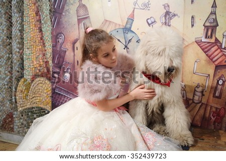 RUSSIA, MOSCOW - 18 DEC, 2014: Little girl (with model release) in evening dress is sitting next to the dog at Aquamarine circus. - stock photo