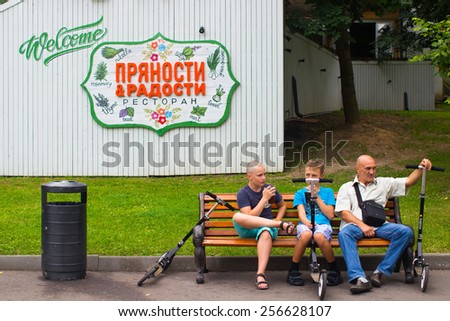 Russia, Moscow, July 8, 2014 - Park of Culture and Rest Gorky. Father and sons sit down to rest on a bench with their scooters. - stock photo