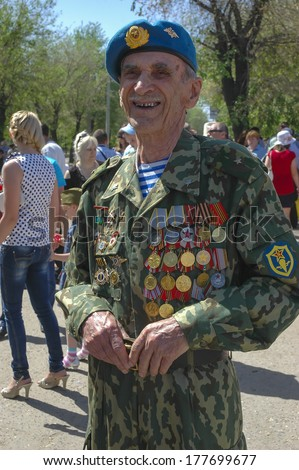 RUSSIA, VOLGOGRAD  MAY 9: Old man veteran of WWII in uniform decorated with numerous orders and medals walks during festivities devoted to 67th anniversary of Victory Day on May 9, 2010 in Volgograd.  - stock photo